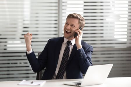 Euphoric successful middle aged male ceo manager talking on phone, listening to good news, celebrating new corporate client attracting. Happy overjoyed lucky businessman reached important goal.