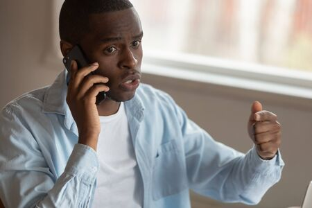 Angry african American millennial man talk explain have unpleasant smartphone call or conversation, mad dissatisfied biracial male talk on cellphone dispute with phone company, bad connection concept Foto de archivo