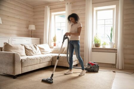 Happy african American young woman preform household chores cleaning living room using modern vacuum cleaner, smiling biracial wife remove dust from home carpet, do housekeeping job Stock Photo - 129610629