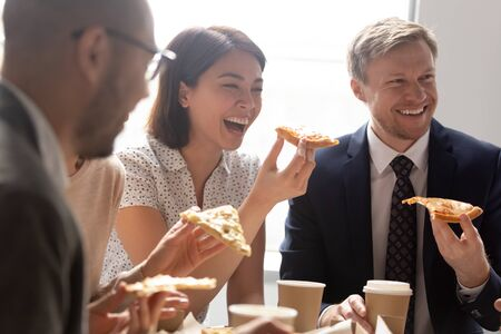 Close up young korean female employee holding slice of pizza, bursting in laugh, listening to colleagues joke. Group of diverse business people gathered at office table, celebrating end of workdays. Stock Photo