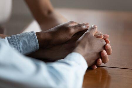 Primo piano di una coppia afroamericana che si tiene per mano sul tavolo di legno per riconciliare la pace dopo il combattimento, marito e moglie birazziali mostrano amore, cura e sostegno, hanno un momento romantico e intimo. Concetto di devozione