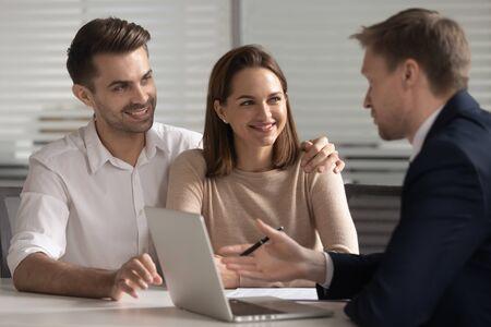 Lächelndes junges Familienpaar, das sich mit Anwalt, Bankangestelltem, Finanzberater oder Immobilienmakler berät. Glücklicher Ehemann und Ehefrau, die Darlehen, Hypotheken, Kauf der ersten Wohnung, Krankenversicherung aufnehmen. Standard-Bild