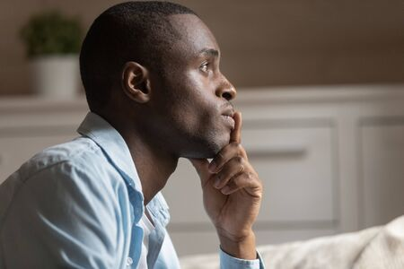 Side profile view of pensive african American man look in distance thinking solving family conflict, thoughtful biracial millennial male have dilemma pondering over problem solving, lost in thoughts