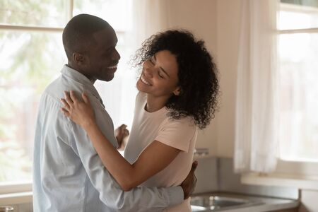 Loving happy millennial african American couple celebrate wedding anniversary dancing swaying in kitchen, smiling biracial husband and wife enjoy romantic date moving relocating to new home