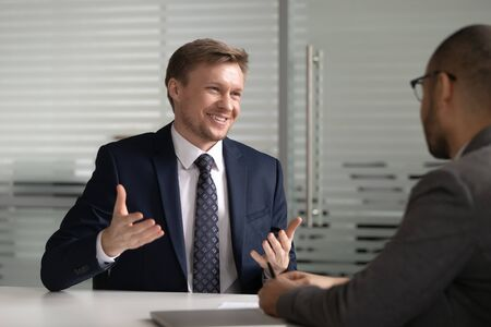 Cheerful ceo sharing company development ideas with african american partner. Smilling male work seeker applicant in suit presenting himself on dream job interview with boss or hr manager at office.