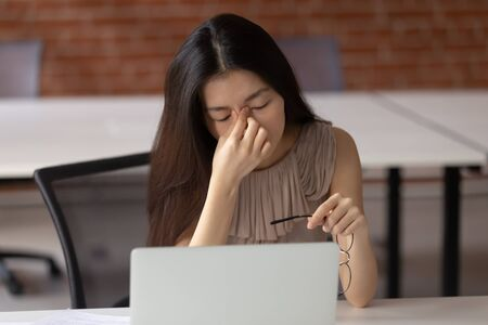Tired asian business woman sitting at office table, taking off glasses, suffering from eyes strain. Exhausted young employee massaging nose bridge, feeling fatigue, overloaded with computer work.