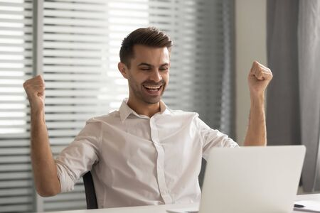 Young happy male employee looking at laptop screen, celebrating job promotion, salary increment or online lottery win. Lucky millennial manager achieved important business goal, received good news. Stockfoto