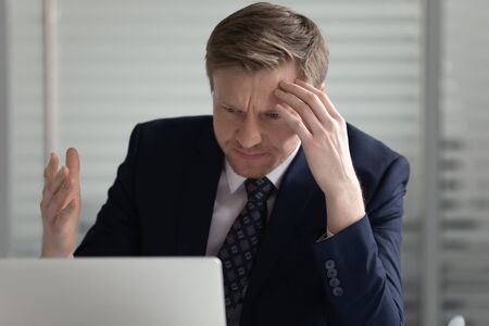 Head shot stressed middle aged male director looking at laptop screen, annoyed by bad news mail, dissatisfied financial report results. Upset manager irritated by poor wifi connection, slow internet. Stockfoto