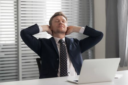 Relaxed positive male manager stretching back, leaning on comfortable chair with folded hands behind head. Mindful calm peaceful middle aged businessman dreaming, having rest in break time at office.
