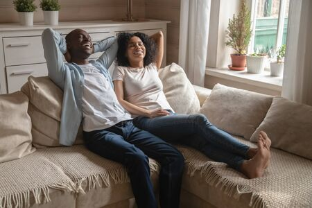 Happy african American husband and wife lying on comfortable couch at home dreaming or visualizing together, smiling biracial young couple relax on cozy sofa take break enjoy calm weekend