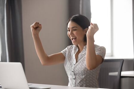 Excited young asian business woman celebrating successful financial project results, attracting important corporate client, dream goal achievement. Euphoric employee got increased salary or promotion. 스톡 콘텐츠