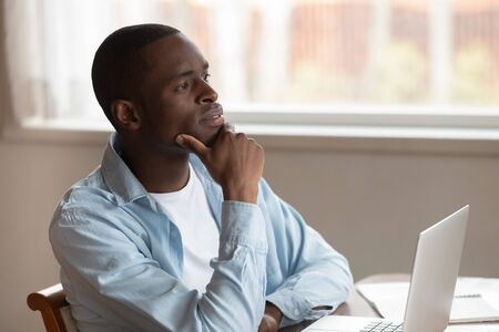 Pensive African American millennial man sit at table distracted from computer work thinking or dreaming, thoughtful biracial male dreamer look in distance pondering, business vision concept