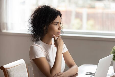 Pensive mixed race ethnicity woman sit work at laptop at home look in distance thinking or dreaming, thoughtful african American female distracted dreaming, pondering having relationships dilemma Imagens