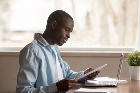 Focused african American millennial man sit at table work study using laptop reading paper document, concentrated biracial male look through consider paperwork letter, good news notice at workplace
