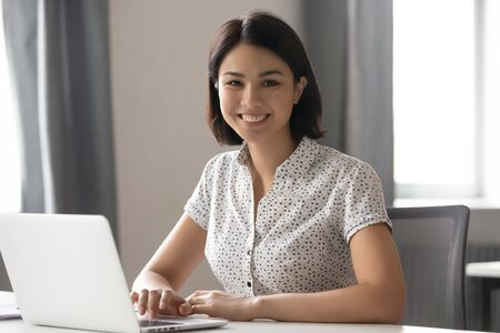 Happy motivated asian female employee hr manager team leader working with computer at modern office portrait. Smiling confident mixed race business woman, professional coach trainer looking at camera.