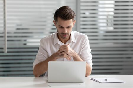 Pensive young businessman sitting at office, looking at laptop screen. Worried professional thinking of problem solution, solving business challenge. Thoughtful manager waiting for project results.