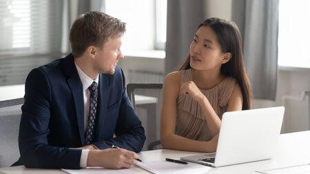 Junge glückliche konzentrierte chinesische Praktikantin, die selbstbewusste männliche Teamleiter mittleren Alters Fragen zur Arbeit stellt. Diverse Mitarbeiter sitzen zusammen im Büro mit Computer und diskutieren Projektideen.