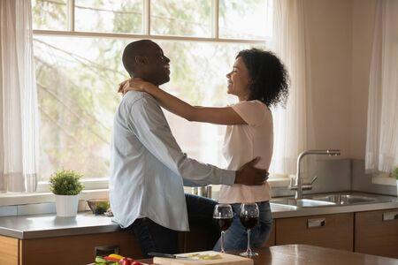 Amorevole felice afroamericano marito e moglie abbraccio godersi cena romantica data in cucina, sorridente coppia birazziale bere vino abbraccio celebrando anniversario di matrimonio a casa, concetto di celebrazione