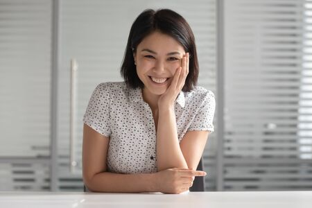 Happy asian woman sitting at table, looking at camera, having video call with friend or client, listening speaker, laughing at joke. Positive young female hr manager holding distant job interview.