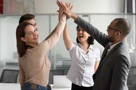 Excited young female team leader looking at camera, giving high five to colleagues, standing at office. Motivated workers celebrating making important decision or business goal teamwork achievement.