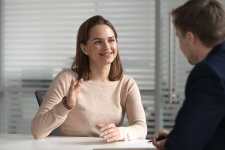 Interested hr male manager or boss holding job interview with young female candidate. Financial advisor, lawyer, real estate agent, bank manager listening to clients wishes or needs at company office. Stock Photo