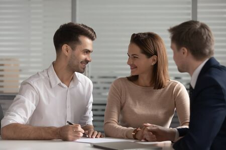 Young happy married family couple looking at each other, making decision before signing contract, considering mortgage or bank loan, meeting with broker, realtor, lawyer, financial advisor at office.