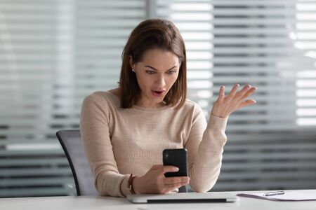 Outraged young female employee holding cellphone in hands, received bad news. Stressed manager annoyed by spam message, broken device, poor internet connection, discharged battery, bad working app. Stock Photo