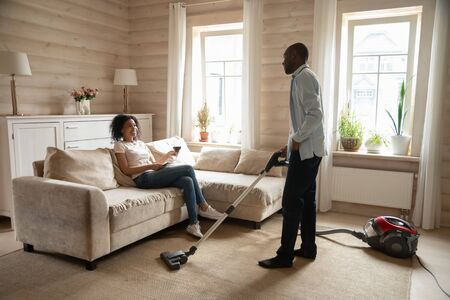 Young african American wife relax on couch in living room drinking wine, biracial husband clean house carpet with vacuum cleaner, mixed race couple share household chores, family role reversal concept