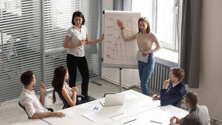 Entraîneurs ou entraîneurs professionnels asiatiques et caucasiens donnant une présentation sur tableau à feuilles mobiles, expliquant des graphiques aux employés concentrés de race mixte dans une salle de conférence moderne, vue de dessus.