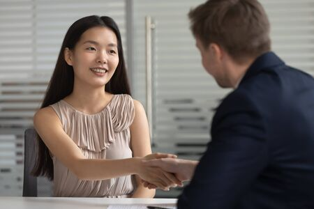 Smiling happy asian young professional shaking hands with hr manager or boss after successful job interview, got hired. Cheerful chinese woman thanking lawyer or real estate agent for consultation.