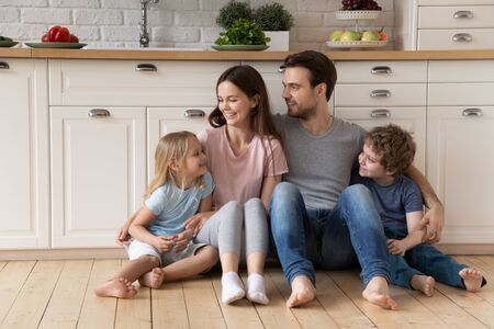 Happy millennial father mother and cute small kids sitting on warm heated wooden floor at modern kitchen, listening to little daughter sister. Smiling family tenants enjoying weekend time together.