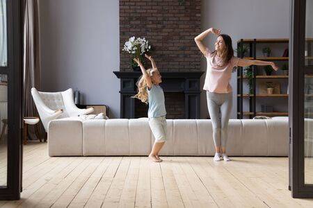 Full length overjoyed young mother dancing to favorite energetic music with little cute adorable smiling daughter in living room. Happy family of two enjoying active time on weekend at home. Фото со стока - 130062023
