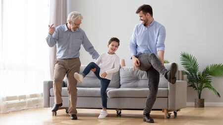 Happy active 3 three generation men family senior old grandfather, young adult dad and cute little kid son grandson dancing having fun playing together enjoy leisure lifestyle in living room at home Stockfoto