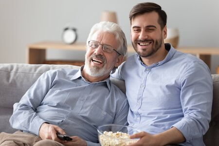 Happy two generations men family old senior father and young adult grown son hold snack remote control bonding watching tv show sit on sofa together having fun laugh view television at home on couch 스톡 콘텐츠 - 130062028