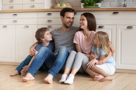 Happy family of four bonding sitting on warm heated wooden floor at modern kitchen. Overjoyed young family couple hugging embracing smiling children siblings, talking, enjoying weekend time together.
