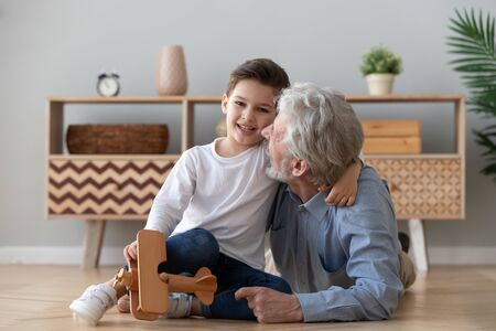 Happy loving old grandad embracing cute small grandson looking at camera, two generations family senior grandfather and grandchild playing wooden plane having fun bonding on floor at home, portrait