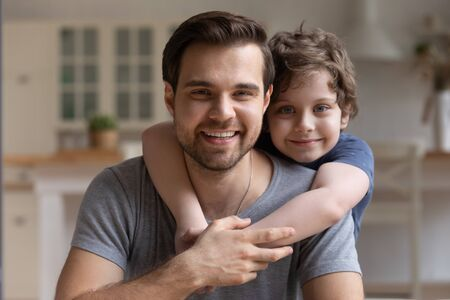 Head shot close up portrait happy little cute boy hugging smiling young father or elder brother. Joyful male family of two looking at camera. Multigeneration relationship, positive emotions concept.
