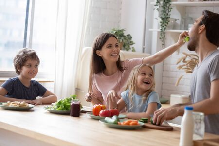 Head shot happy full family sitting at huge kitchen table, cooking together, preparing salad for dinner, overjoyed little children siblings looking how young smiling mommy feeding funny father.