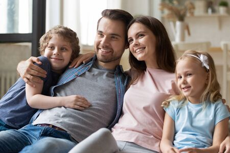 Happy parents sitting with smiling children siblings at comfortable couch in living room, enjoying spending free weekend time together. Joyful family of four cuddling, bonding, entertaining at home.