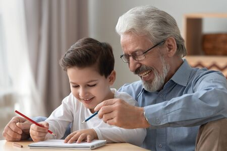 Happy two 2 generations family old grandfather helping teaching cute little boy grandson drawing with pencils together, smiling senior grandpa playing with grandchild enjoy creative children activity