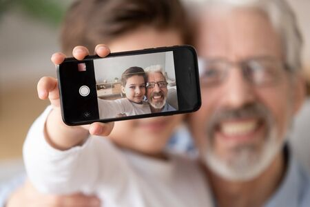 Cute little boy grandson embrace happy old grandfather hold phone take selfie, two generation family small grandchild and senior grandparent bonding make photo self portrait, focus on mobile display Stockfoto