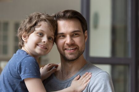 Head shot portrait young smiling father holding little preschool son on hands, looking aside. Happy small boy kid embracing handsome daddy, two generations, warm friendly family relations concept. 版權商用圖片