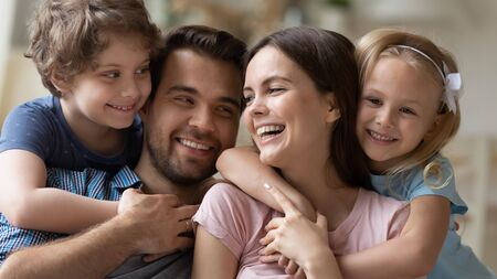Head shot close up family portrait positive parents hugging little son and daughter, feeling joyful. Happy young married couple having fun, joking, laughing with cute school children at living room.