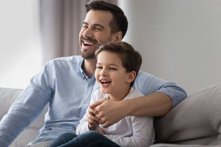 Happy young dad and cute small kid son laughing watching funny comedy movie tv show sitting on sofa, cheerful father having fun with child boy viewing television together at home relaxing on couch