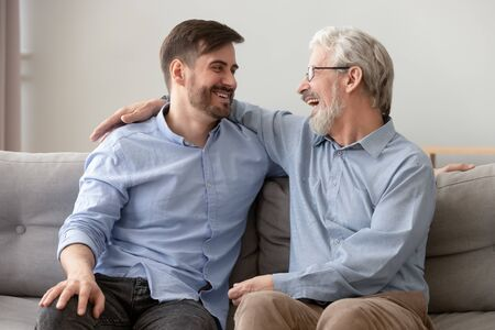 Happy old senior dad embracing young adult grown son talking laughing sit on sofa at home at reunion meeting, two generations male family relaxing having fun enjoy bonding together on fathers day