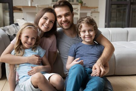 Portrait of happy full bonding family of four, sitting at warm wooden heated floor in living room at home. Smiling lovely young parents hugging little cute children siblings, looking at camera. 免版税图像