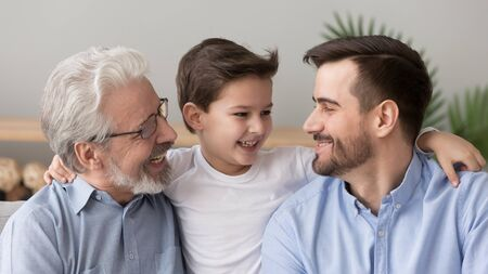 Cute happy little boy son grandson embracing young father and old elder grandfather laughing hugging at home, multi three 3 generation men family grandparent parent and grandchild bonding together