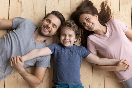 Above top view happy adopted little kid boy holding hands of smiling young family couple, enjoying weekend time together. Playful son lying between joyful parents on heated wooden floor at home.