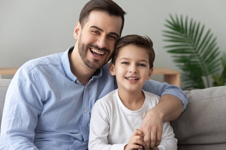 Happy male family cheerful young adult single dad embracing cute child preschool boy looking at camera, smiling father hugging little kid son bonding laughing sit on sofa at home, close up portrait