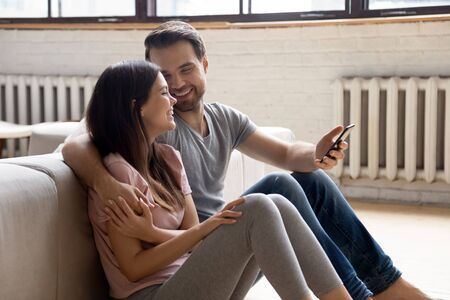 Loving young married couple sitting on warm heated wooden floor, having fun together. Happy family spouse laughing, embracing, enjoying spending together weekend leisure time in living room at home.